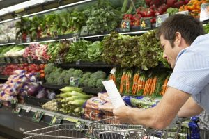 Man in supermarket looking at his list