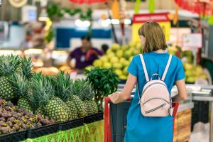 Woman with cart shopping at supermarket