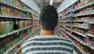 back of man as he walks down supermarket aisle