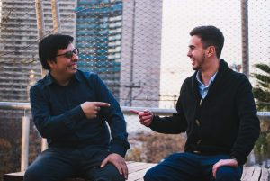 Two men pointing to each other and smiling