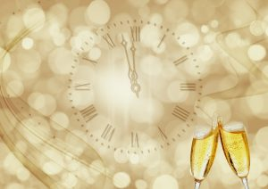 Clock at midnight and champagne glasses