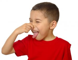 kid holding his nose and sticking out his tongue