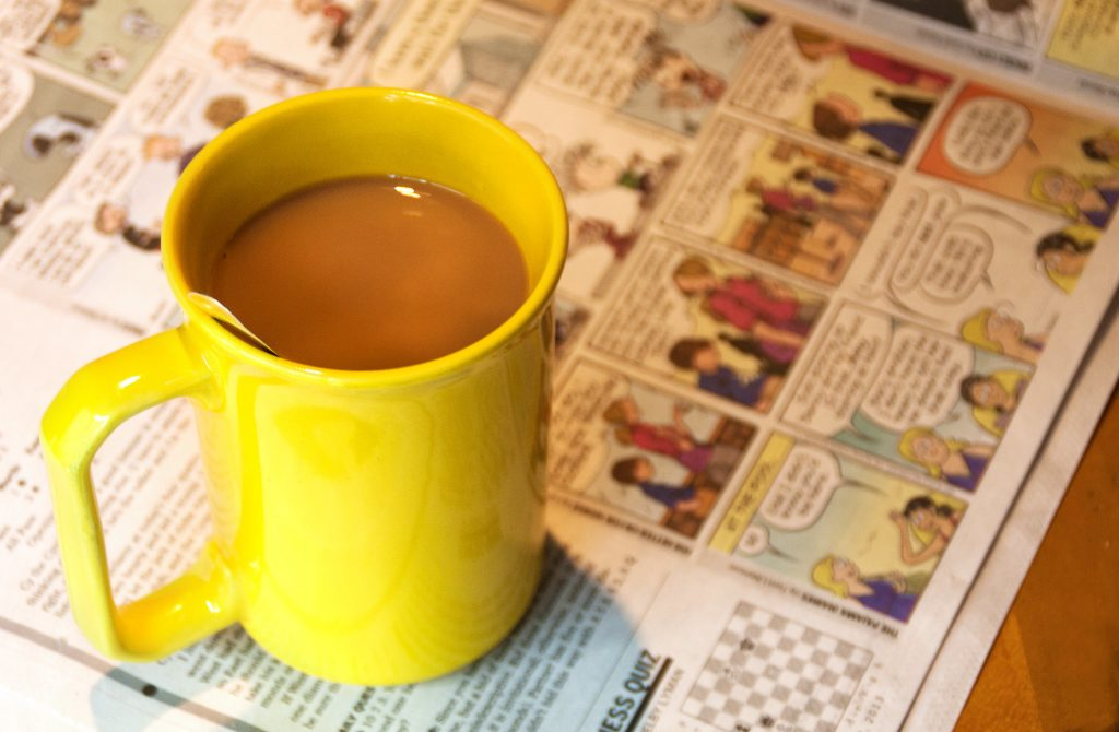 Yellow cup of coffee and funny pages from newspaper