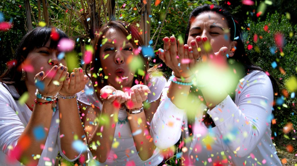 3 women blowing confetti from their hands