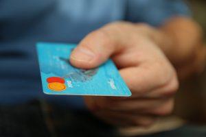 Man's hand holding a debit card