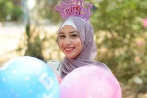 smiling woman wearing a hijab, holding balloons and wearing Happy Birthday crown