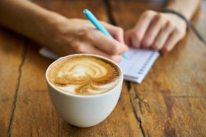 man's hands writing on notepad wood plank table espresso coffee