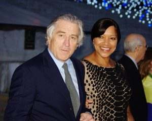a person with darker skin and lighter skin in formal attire, holding hands