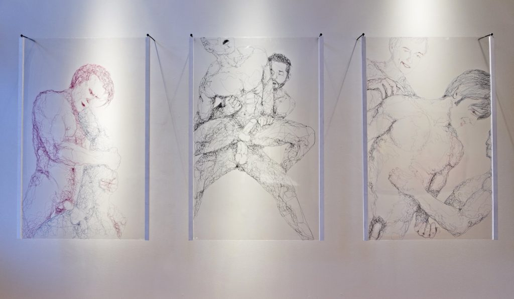 Three panels of thread art depicting nude males.