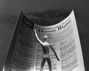 Photo illustration of a figure standing in front of a paper by the universal declaration of human rights bill