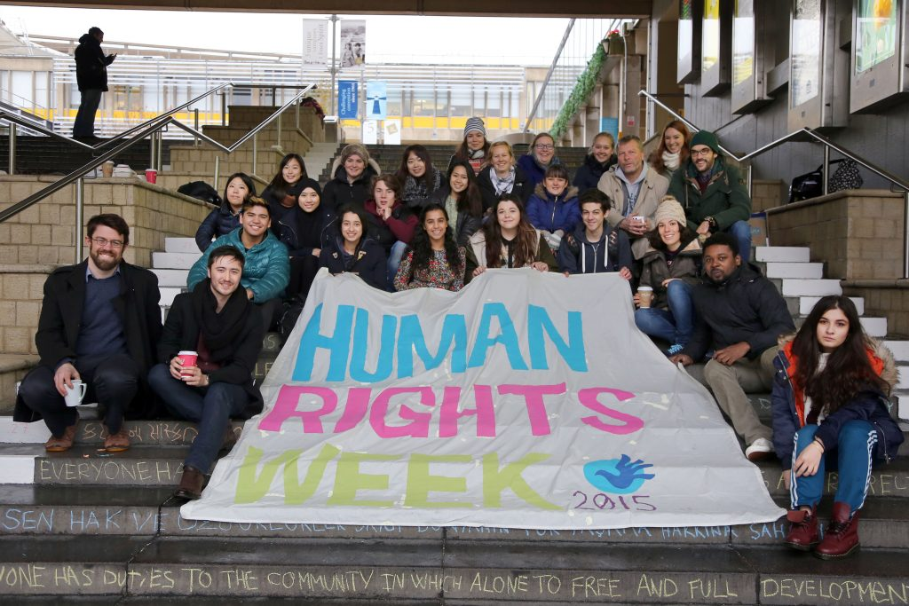 Photo of young people sitting on stairs holding a Human Rights Week banner