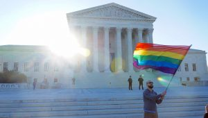 Photograph of a person waving a rainbow colored flag in front of the Supreme Court of the USA.