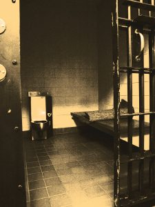 Stylized photograph of a jail cell.