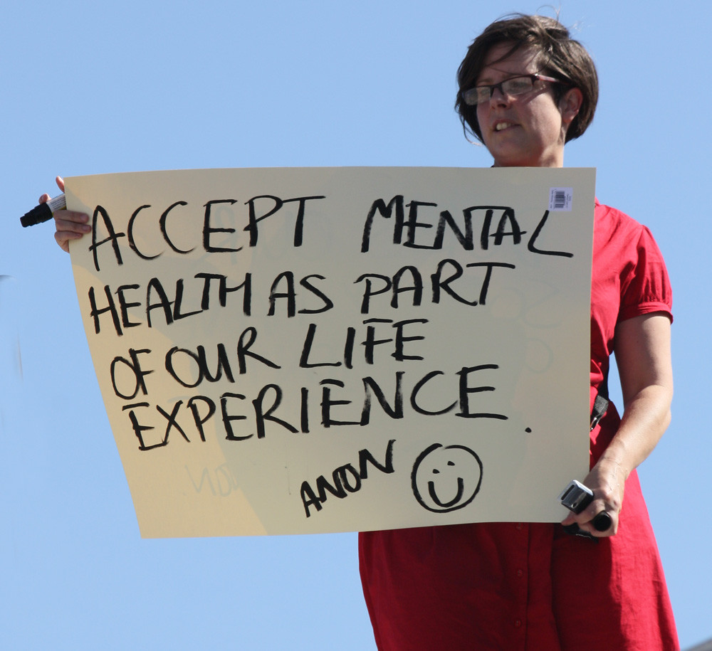 Woman in red dress holding sign that says Accept Mental health as part of our life experience.
