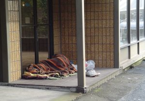 Photo of a person with a blanket, sleeping in the front of a building.