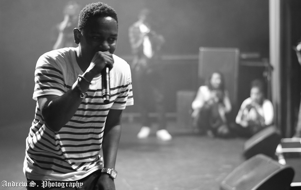 Kendrick Lamar holds a microphone close to his mouth