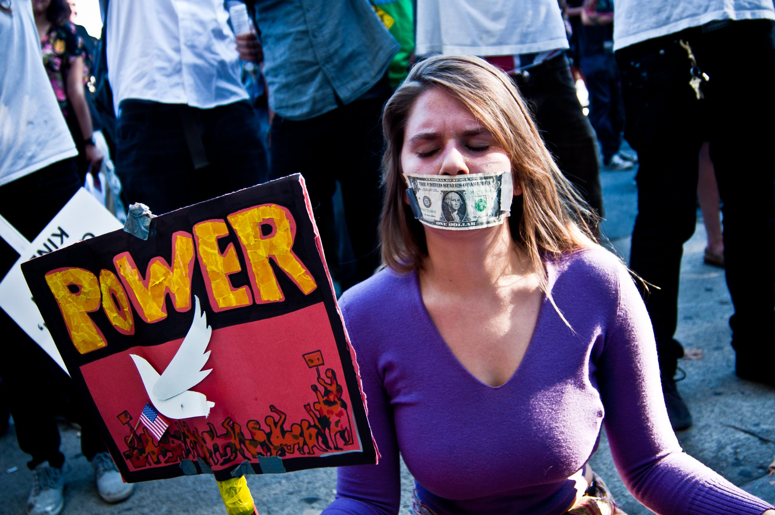 Photograph of a woman with a sign saying POWER. She has a dollar bill taped to her mouth.