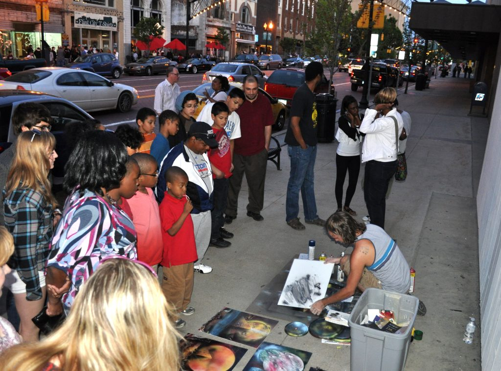 Photograph of people on the streets watching an artist making art.