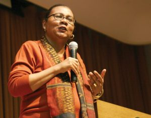 Photograph of bell hooks speaking with a microphone in her hand.