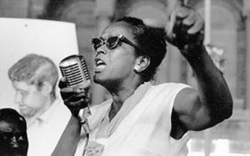 Photograph of human rights activist Ella Baker speaking into a microphone with her fist raised.