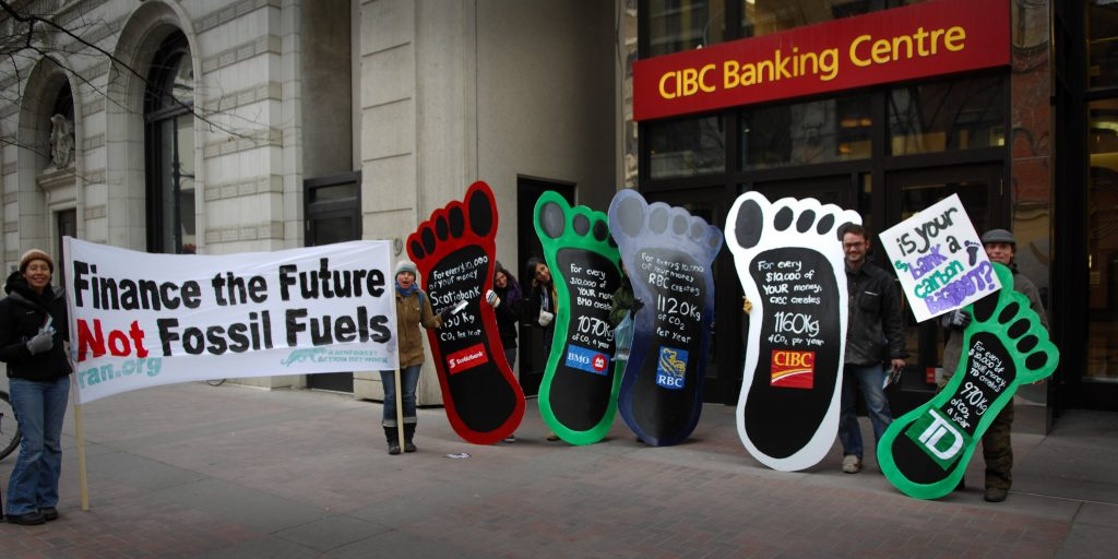 Photograph of people holding posters of large feet in front of a bank protesting.