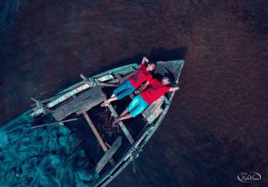 Overhead photograph of man and woman of India laying on their backs on in a row boat.