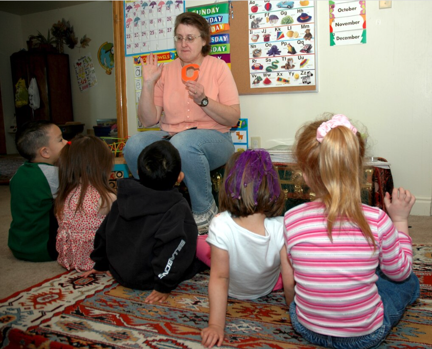 Photo of a woman sitting holding a letter C with children sitting on the floor watching her.
