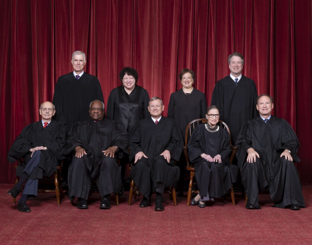 Nine Supreme Court Justices in black robes posing in front of a red curtain.