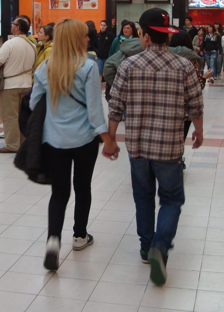 Photograph of a woman and man holding hands walking in a mall.