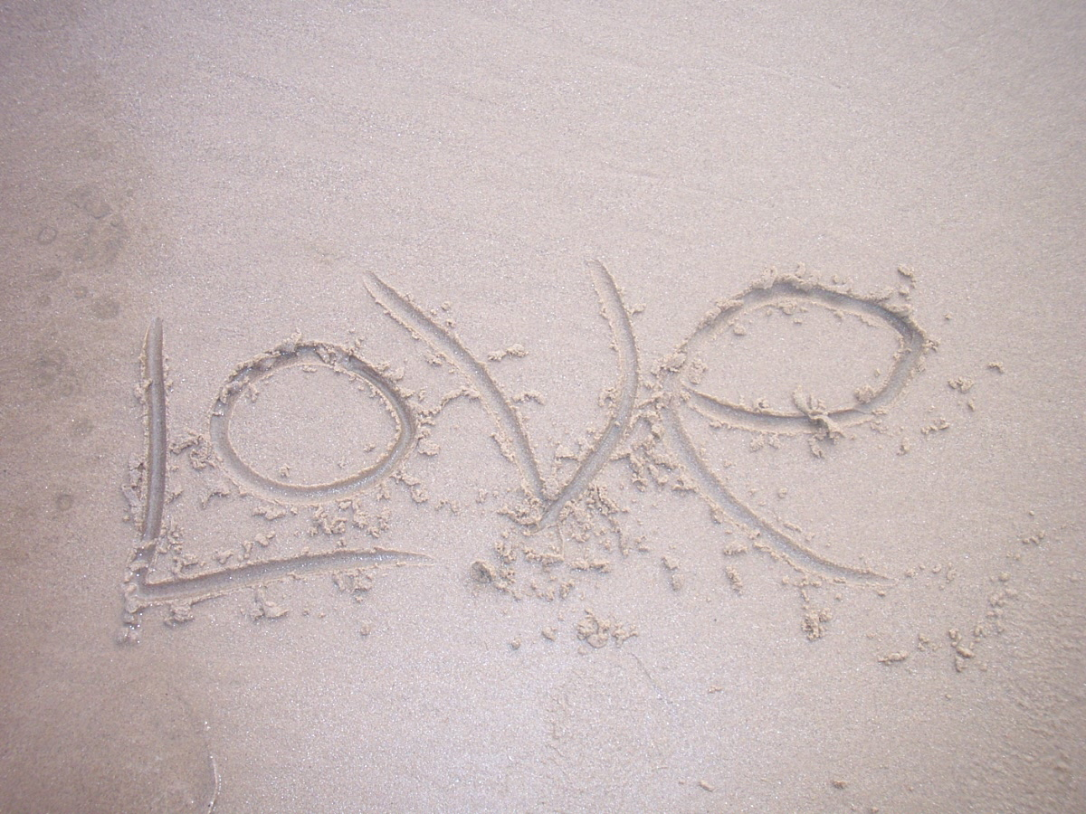 The word love written in the sand.
