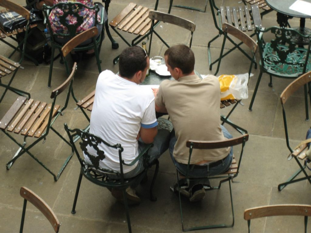 Overhead photograph of two men sitting next to each other at a small table.