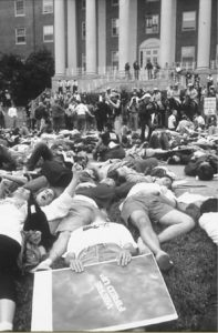 Black and white photo of thousands of demonstrators lying down on the lawn, surrounded by police on horseback, in front of a building with pillars.