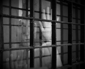prison cell bars in foreground with human hand and face in background