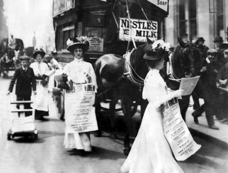 Photograph of women in 1908 in London England carrying signs and marching for women's right to vote.