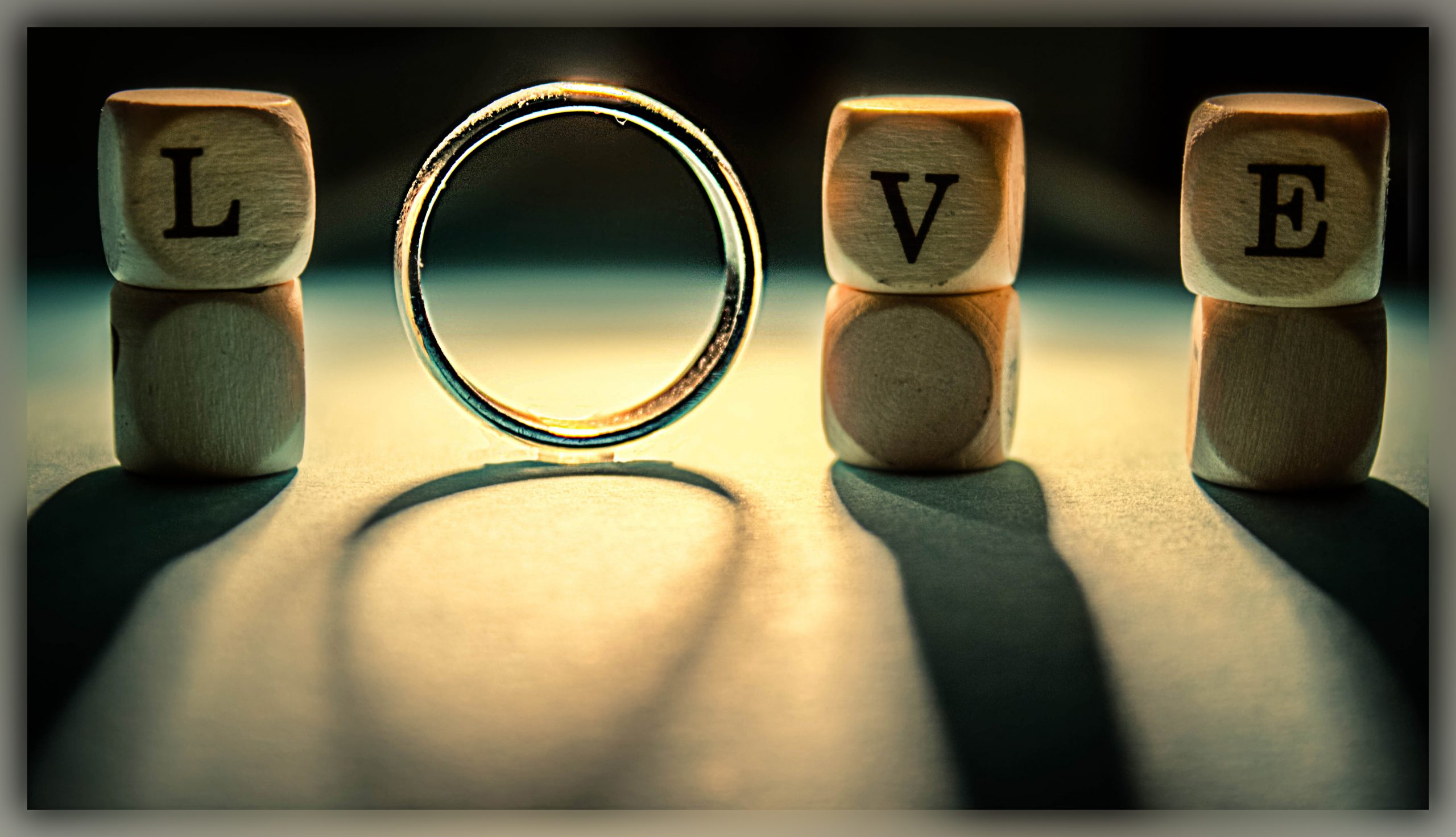 The word love. The letters L, V and E are in wooden blocks. The letter O is represented by a wedding ring.