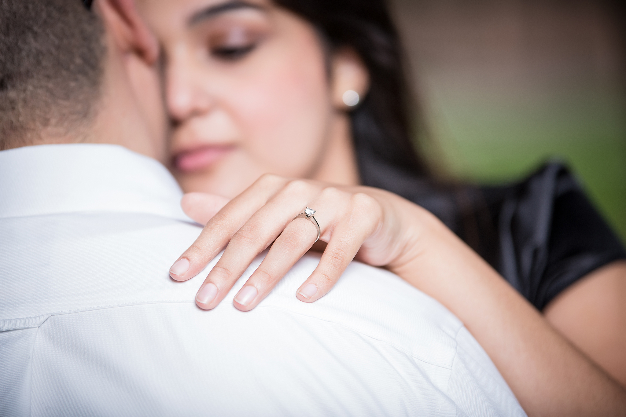 A man's shoulder with a woman looking at him with her hand on his shoulder and a ring on her finger.