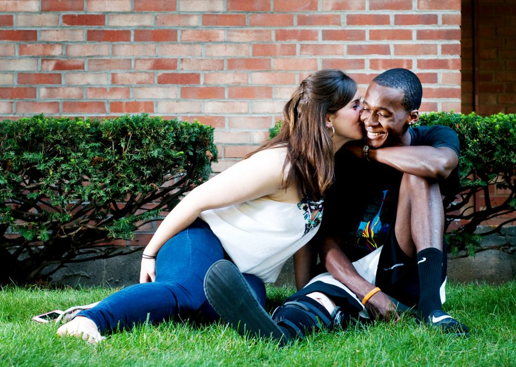 a white young woman kissing a Black young man on the cheek while sitting on a lawn.