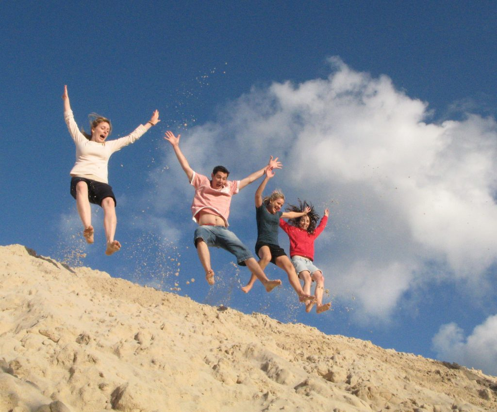 photo of four people jumping in the air