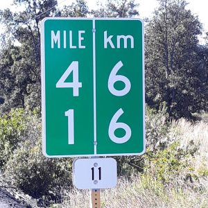 Hawaii: a road sign stating that 13 miles equals 21 kilometers