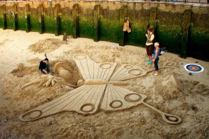 an artist working on a sand sculpture of a butterfly while some bystanders watch