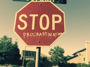 "a stop sign with the word ""procrastination"" painted beneath the word ""stop"""