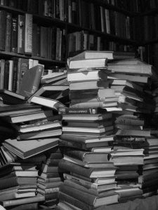 several large messy stacks of books on a table in a library