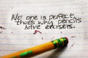 "photo of a pencil eraser attempting to erase the words ""no one is perfect, that's why we have erasers"" written in ink"