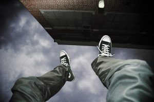 "a photo titled ""Falling Upside Down"" shows a person's legs and feet upside down next to a building with the sky visible beyond their feet"