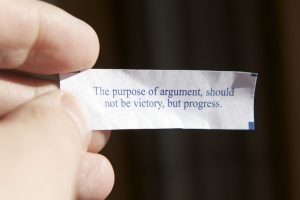 "a picture of a hand holding a fortune from a fortune cookie; the fortune reads ""The purpose of argument should not be victory, but progress."""