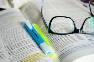glasses and highlighter pens sitting on an open textbook