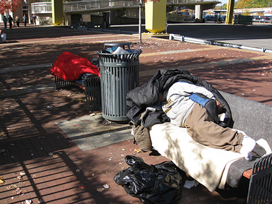 The image is a photograph of two people who are homeless and sleeping on public city benches.