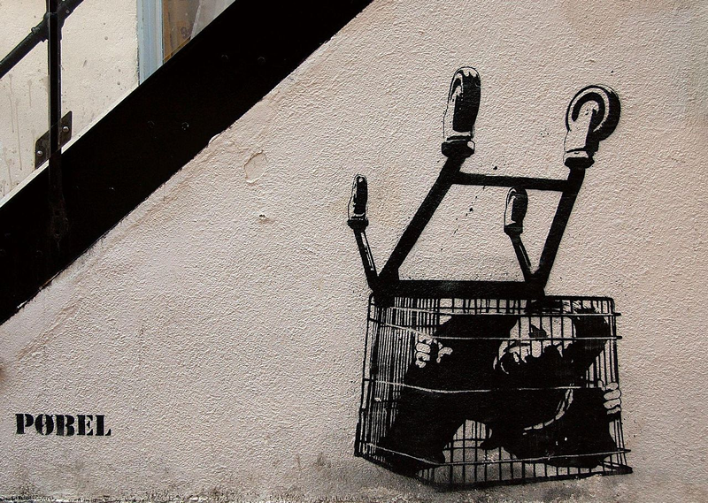 Graffiti depicting a screaming person trapped in the cage of an overturned shopping cart