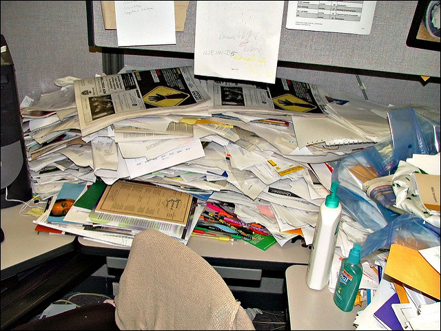 very messy office, desk covered in papers