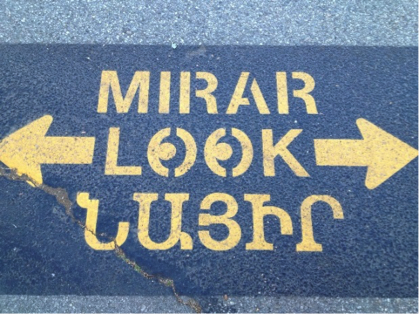 painted sidewalk sign with the word look in Spanish, English and Armenian